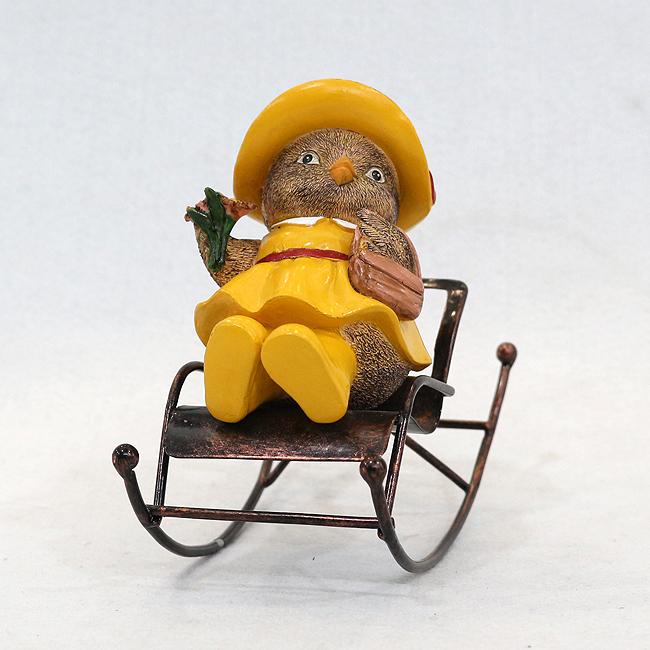 흔들이 의자에 앉은 병아리 여사 조각상